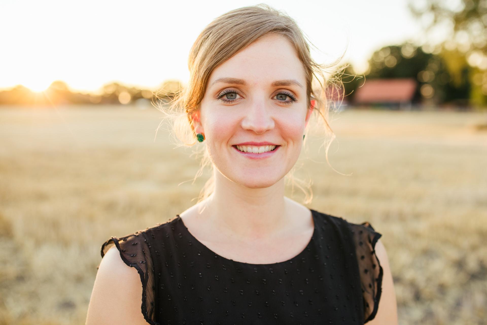 Frau im Abendlicht auf einem Feld – Gegen die Sonne fotografieren